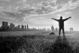 Stonehenge bij opkomende zon met mediterende staande man met omhoog geheven armen